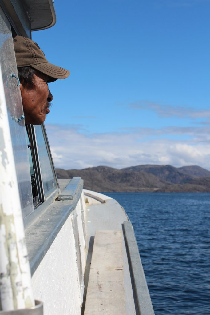 A man with a moustache looks out the window of his small boat.