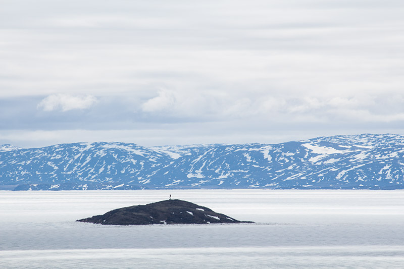 A small hit protrudes from the sea ice surrounded by snow covered mountains